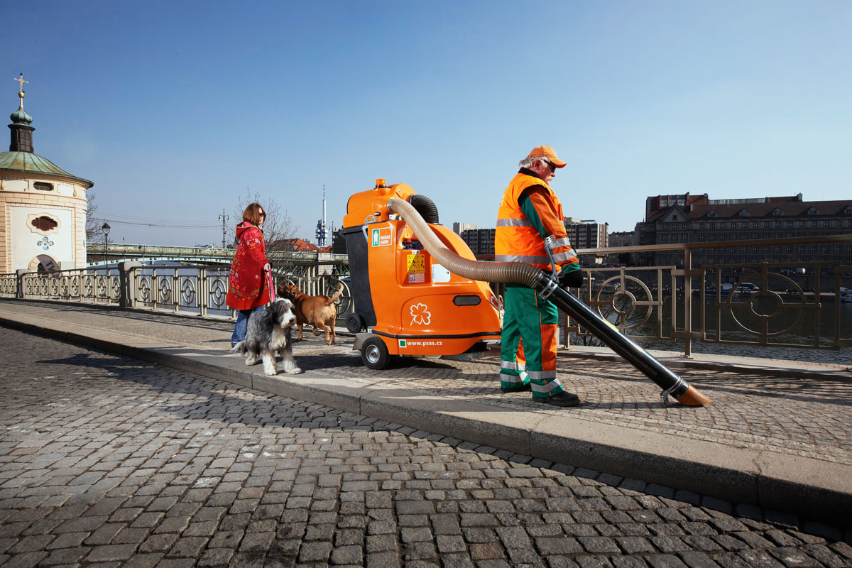 A man cleans the streets near a river with the Glutton street cleaner