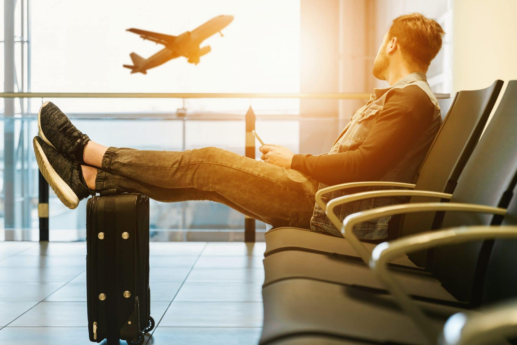 Man waits in airport as plane takes off in the background