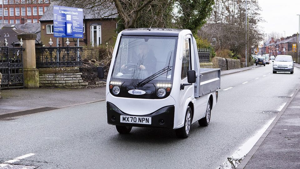 Man driving X Cell Electric Vehicle